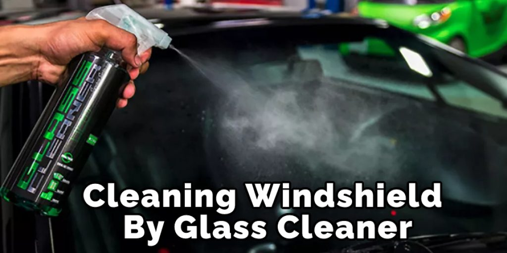 Cleaning Windshield By Glass Cleaner
